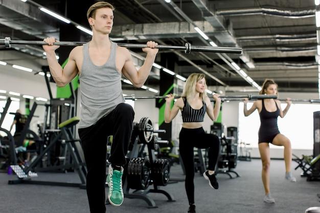 Esporte, musculação, estilo de vida e conceito dos povos - homem novo e duas mulheres com barra que dobram os músculos e que fazem a imprensa do ombro agachar-se no gym