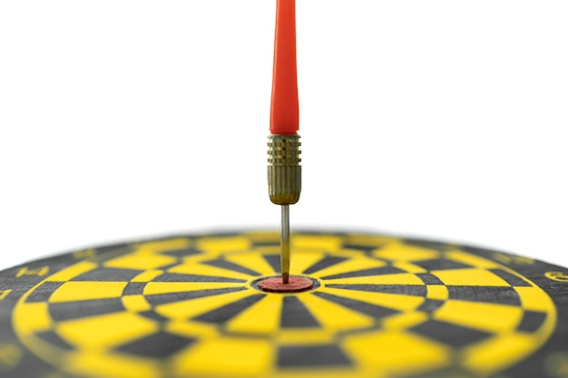 Esporte, negócio, objetivo, planejamento e conceito de destino. close up da renda de dardo vermelho atingido no centro do alvo de dardos preto e amarelo