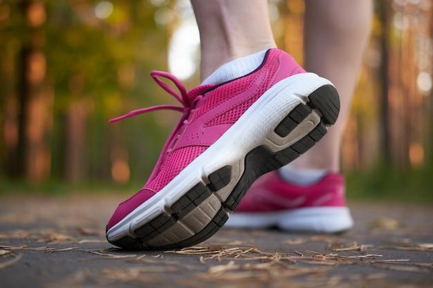 Esporte. pernas femininas de tênis rosa na execução de julgamento na floresta. close-up em sapatos esportivos de uma mulher correndo. corre
