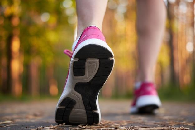 Esporte. pernas femininas em tênis rosa na execução de julgamento na floresta. close-up em calçados esportivos de uma mulher correndo. execução do conceito