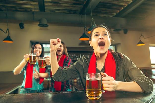 Esporte, pessoas, lazer, amizade, conceito de entretenimento - fãs de futebol feminino felizes ou bons jovens amigos bebendo cerveja, comemorando a vitória em um bar ou pub. conceito de emoções positivas humanas