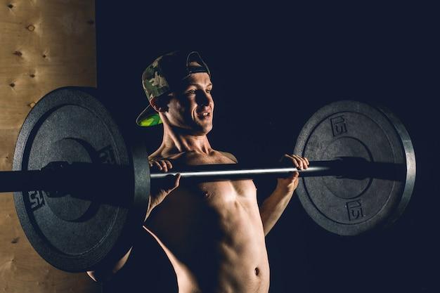 Esporte, treino. closeup retrato de um treino de homem musculoso com barra no ginásio.