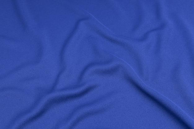Esporte vestuário tecido textura de fundo. vista superior da superfície de têxteis de pano. camisa azul do futebol com copyspace.