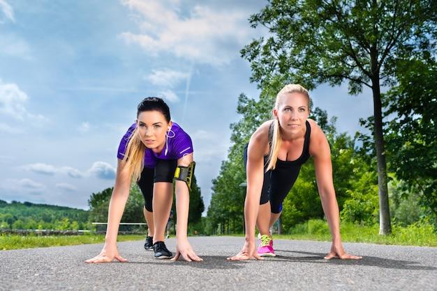 Esportes ao ar livre - mulheres jovens fazendo fitness no parque