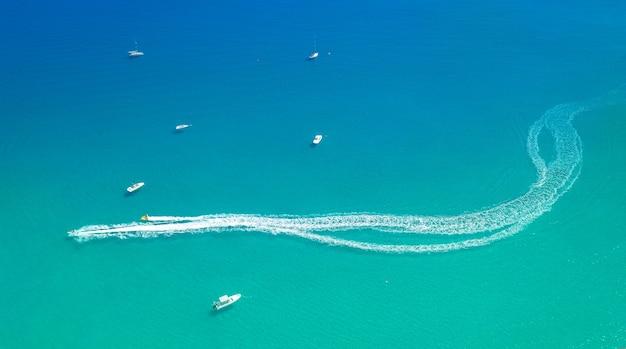 Esportes aquáticos no fundo mínimo aéreo à beira-mar. lanchas deixam rastro de borrifo na água do mar