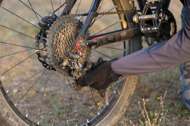 Esportes brutal barbudo em uma mountain bike um ciclista nas colinas verdes está consertando uma bicicleta