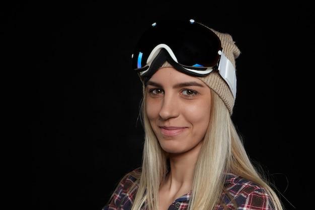 Esportes de inverno e conceito de estilo de vida ativo. mulher europeia jovem e atraente, alegre, snowboarder com cabelo loiro solto, posando com elegantes óculos de segurança na cabeça e sorrindo