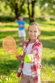 Esportes de verão. menina loira sorridente com camisa xadrez e raquete de tênis estendendo a bola para a frente no gramado verde e meninos à distância
