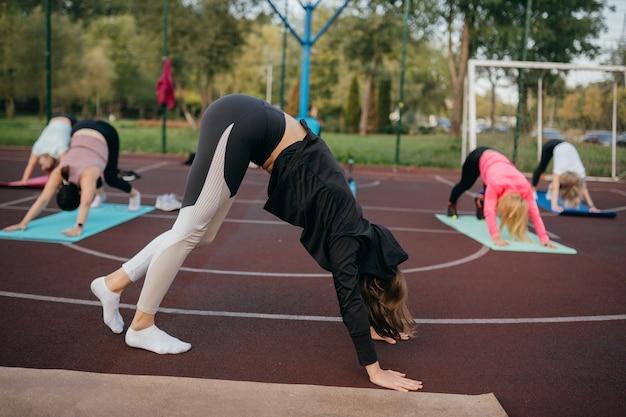 Esportes e fitness fora do ginásio. jovem apta a mulher em trajes esportivos treina ao ar livre no playground.