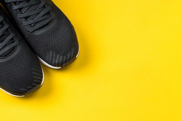 Esportes executando tênis pretos sobre fundo amarelo