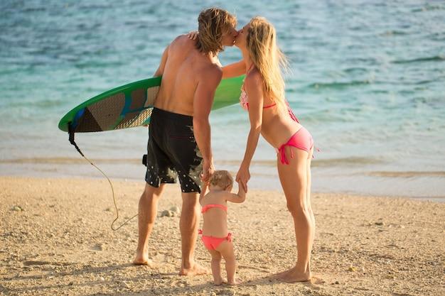Esportes família pai mãe e filha caminhando na praia