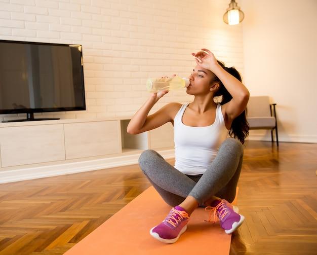 Esportes linda mulher bebendo água enquanto está sentado no tapete de ioga em casa