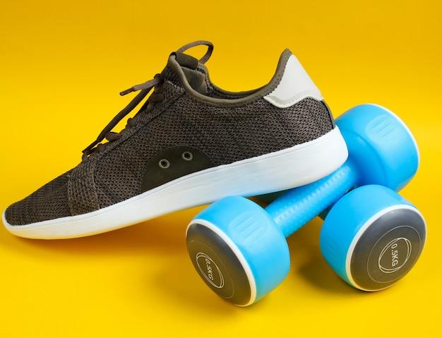 Esportes tênis e halteres na mesa amarela.