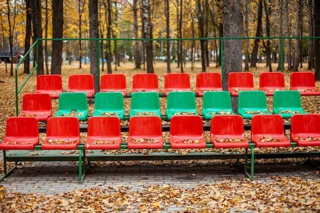 Esportes vazios fica com assentos vermelhos e verdes em um dia de outono.