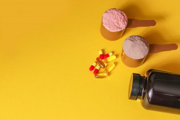 Esportes vitaminas e drogas médicas. duas colheres de medição de proteína de soro de leite