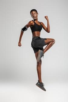 Esportista afro-americana usando celular e fones de ouvido enquanto se exercita isolada sobre uma parede branca