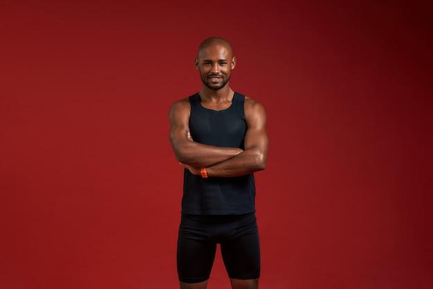 Esportista alegre jovem afro-americano bonito, mantendo os braços cruzados e olhando para a câmera com