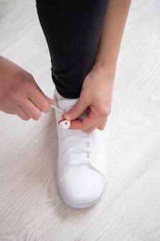 Esportista amarrando tênis branco