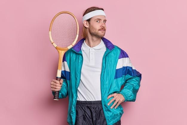 Esportista ativo e autoconfiante mantém a raquete de tênis se gabando de ter vencido a competição vestido com roupas esportivas e gosta de jogo