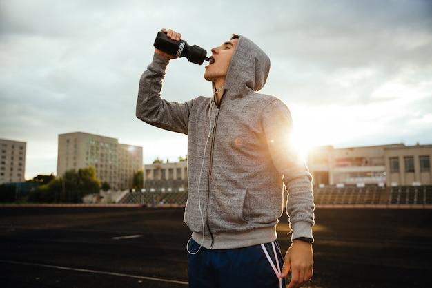 Esportista bebendo água depois de correr, malhar, com fones de ouvido