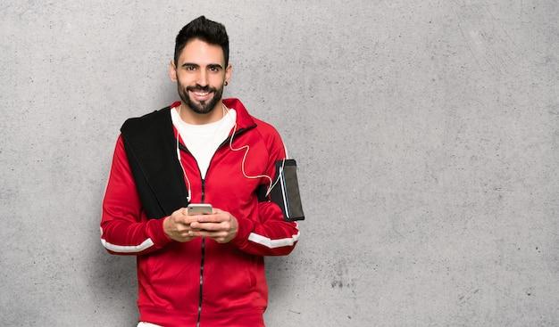 Esportista bonita, enviando uma mensagem com o celular sobre a parede texturizada