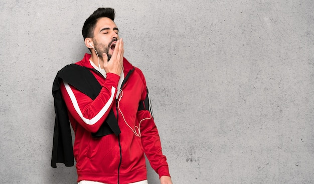 Esportista bonito bocejando e cobrindo a boca aberta com a mão sobre a parede texturizada