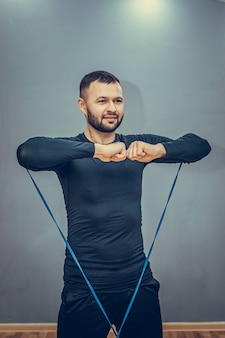Esportista bonito, motivado e focado, realiza agachamentos com corda de resistência