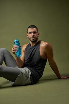 Esportista cansado segurando uma garrafa azul na mão enquanto olha para a câmera isolada no verde