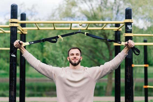 Esportista caucasiano na barra durante o treino de rua. estilo de vida saudável e conceito de esporte de rua