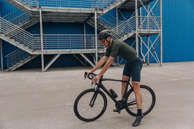 Esportista caucasiano sentado em uma bicicleta preta sobre a parede azul