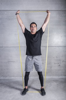 Esportista com elástico segurando os braços levantados