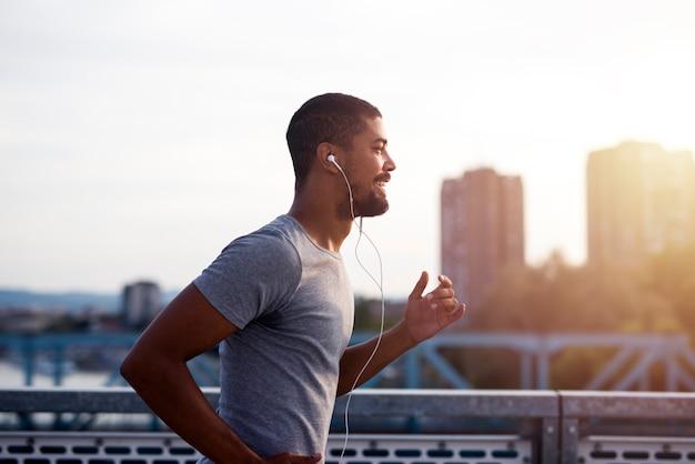 Esportista com fones de ouvido correndo e curtindo