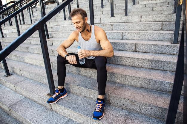 Esportista com garrafa de água está descansando e verificando seu relógio inteligente após a corrida. fitness, esporte, exercício e conceito de estilo de vida saudável de pessoas.