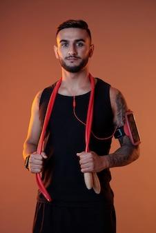 Esportista confiante com fones de ouvido e pular corda