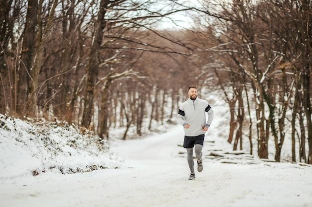 Esportista, correndo na natureza na neve no inverno. estilo de vida saudável, fitness de inverno, clima frio