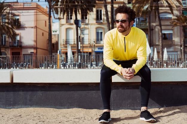 Esportista de blusão amarelo fazendo uma pausa