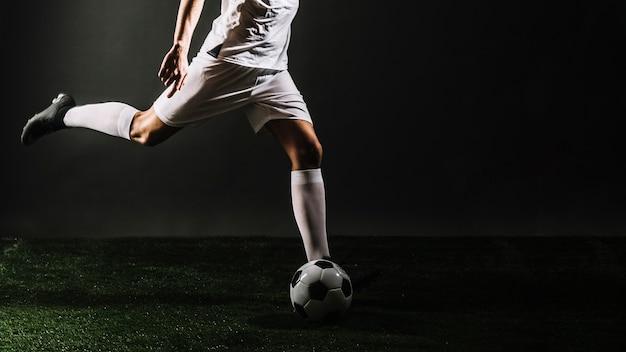 Esportista de colheita chutando a bola de futebol