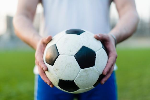 Esportista de colheita mostrando a bola de futebol