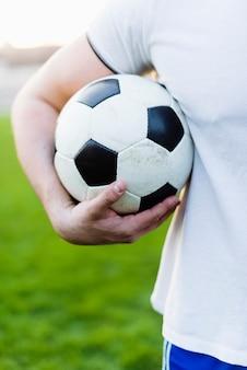 Esportista de colheita segurando a bola