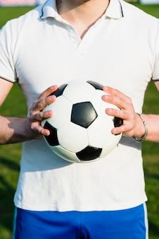 Esportista de colheita segurando uma bola de futebol nova