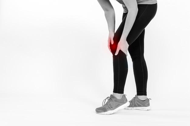 Esportista de colheita tocando joelho machucado