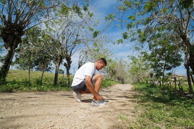Esportista de corredor amarrando cadarços na natureza.