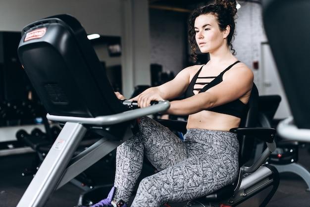 Esportista de fitness em moda sportswear ciclismo na academia, exercitando pernas fazendo ciclomotores de ginástica cardio. vestuário e sapatos esportivos, estilo urbano.