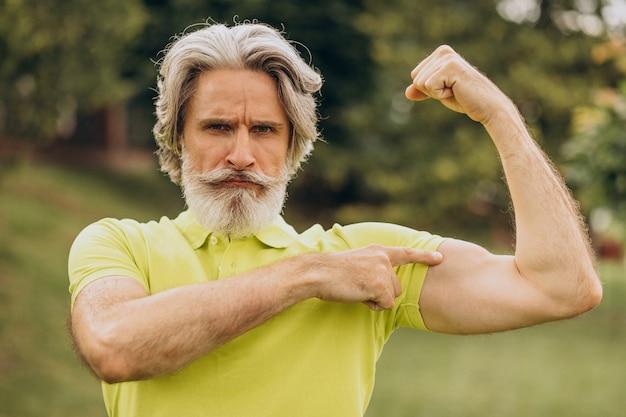 Esportista de meia-idade apontando no bíceps
