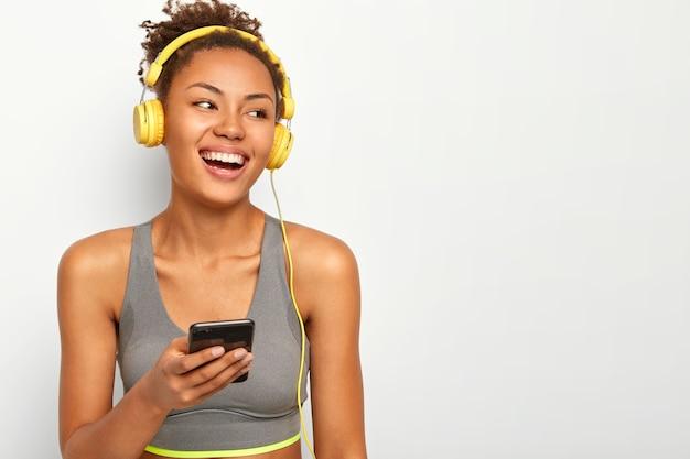 Esportista de pele morena exultante ri de emoções agradáveis, segura celular moderno, vira as costas, vestida com roupas esportivas, tem treino ativo com música