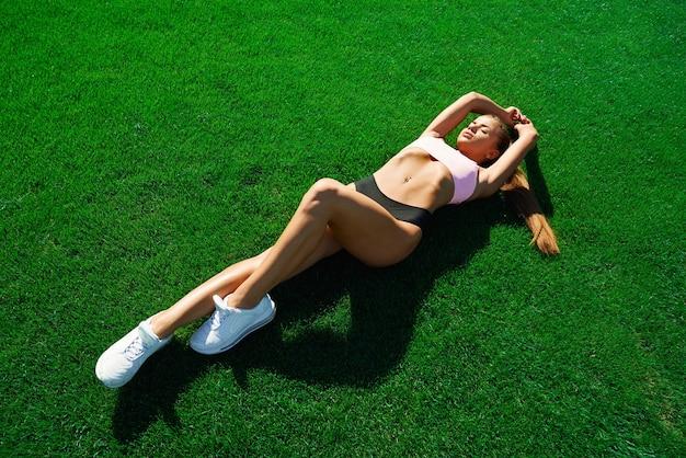 Esportista deitada na grama no campo do estádio