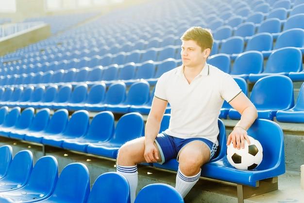 Esportista e bola de futebol no estádio