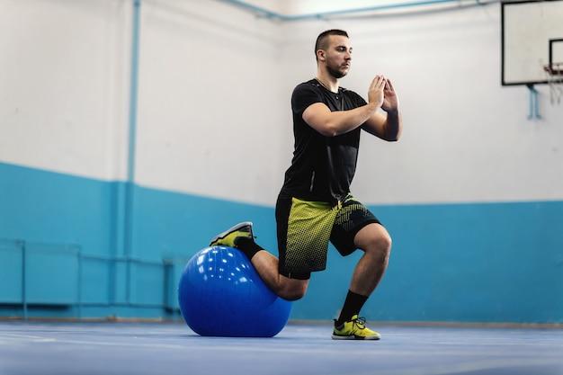 Esportista em boa forma, fazendo estocadas com bola de pilates no salão de esportes.