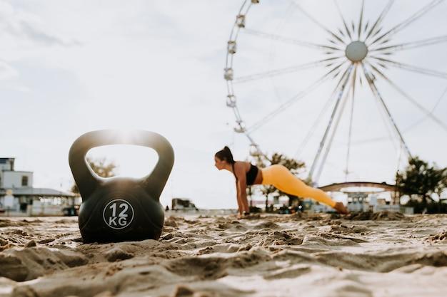 Esportista em forma e tonificada malhando em uma academia de treinamento funcional na praia
