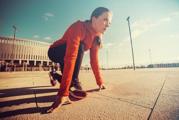 Esportista em posição pronta para correr. menina ajoelhada, preparando-se para começar a correr. conquistas e objetivos